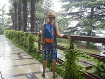 El adolescente con una mochila cuesta debajo de una lluvia del verano Imagenes de archivo