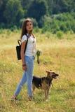 El adolescente consigue la diversión en la granja con el perro Imagen de archivo