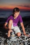 El adolescente crea la pirámide del guijarro en la costa Imagen de archivo libre de regalías