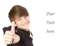 El adolescente da los pulgares encima de la muestra Imagen de archivo