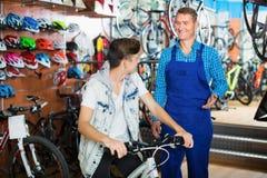El adolescente de ayuda del vendedor del hombre elige la nueva bicicleta Foto de archivo libre de regalías