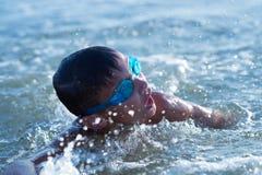 El adolescente de diez años del muchacho nada en el mar Fotografía de archivo