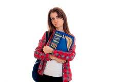 El adolescente de empollamiento en camisa de tela escocesa mira al lado y a sostener una carpeta Fotos de archivo