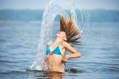 El adolescente de la muchacha con salpica del pelo en el lago Fotos de archivo