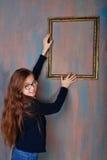 El adolescente de la muchacha corrige un marco vacío Fotografía de archivo