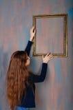 El adolescente de la muchacha corrige un marco vacío Imágenes de archivo libres de regalías