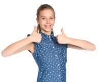 El adolescente de la muchacha detiene un pulgar Imagenes de archivo
