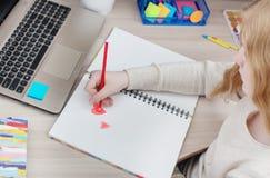 El adolescente de la muchacha dibuja el corazón rojo Imagen de archivo libre de regalías