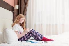El adolescente de la muchacha dibuja en cama Fotos de archivo libres de regalías