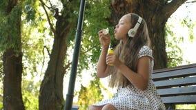 El adolescente de la muchacha en auriculares se sienta en un banco y sopla burbujas de jabón y sonríe metrajes