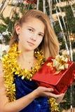 El adolescente de la muchacha en un vestido elegante lleva a cabo un regalo de Navidad Imagen de archivo libre de regalías