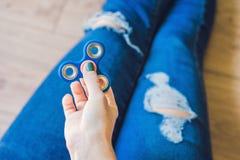 El adolescente de la muchacha en vaqueros holey se sostiene en manos y juegos con el spinn Fotografía de archivo