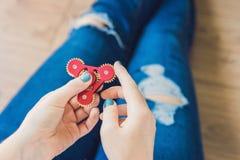 El adolescente de la muchacha en vaqueros holey se sostiene en manos y juegos con el spinn Imagen de archivo