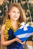 El adolescente de la muchacha en vestido elegante lleva a cabo un regalo de Navidad Foto de archivo