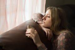 El adolescente de la muchacha falta la ventana con su smartphone Fotografía de archivo