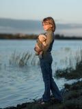 El adolescente de la muchacha se coloca con el juguete y mira la puesta del sol en el lago Fotos de archivo libres de regalías