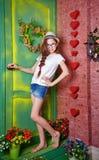 El adolescente de la muchacha se coloca en el pórtico de la casa de campo Foto de archivo