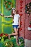 El adolescente de la muchacha se coloca en el pórtico de la casa de campo Foto de archivo libre de regalías