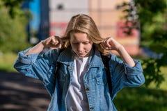 El adolescente de la niña Verano en naturaleza Vestido en ropa del dril de algodón detrás de la mochila El gesto cierra los oídos Fotografía de archivo