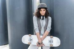 El adolescente de moda está descansando con el auricular en aire abierto Foto de archivo