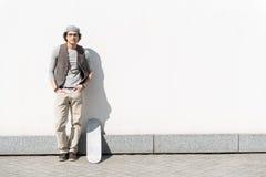 El adolescente de moda se está colocando al aire libre con el monopatín Fotografía de archivo