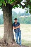 El adolescente de moda se sienta cerca de un árbol escucha la música en naturaleza Fotografía de archivo libre de regalías