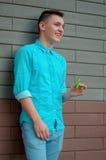 El adolescente de risa en la camisa azul y los tejanos dan el holdin Fotos de archivo