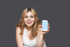 El adolescente de risa está mostrando un teléfono elegante Foto de archivo libre de regalías