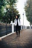El adolescente del muchacho camina en la calle en un otoño Foto de archivo