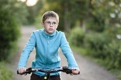 el adolescente del muchacho con los vidrios en la bici monta a lo largo de una carretera nacional Fotografía de archivo libre de regalías