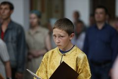 El adolescente del muchacho desempeña servicios en iglesia Imágenes de archivo libres de regalías
