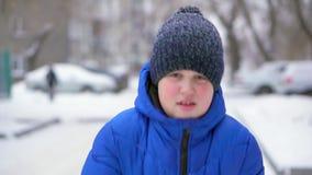 El adolescente del muchacho en una chaqueta azul del plumón lanza nieve Invierno, nieve que cae, primer almacen de metraje de vídeo