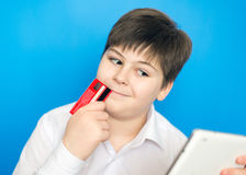 El adolescente del muchacho hace una compra en Internet Foto de archivo libre de regalías