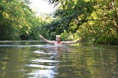El adolescente del muchacho nada en el río en verano Fotografía de archivo