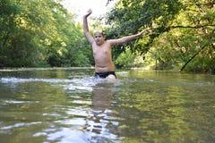 El adolescente del muchacho nada en el río en verano Fotos de archivo