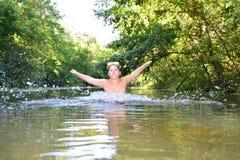 El adolescente del muchacho nada en el río en verano Foto de archivo