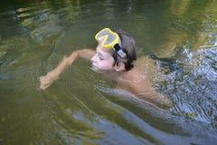 El adolescente del muchacho nada en el río en verano Foto de archivo libre de regalías