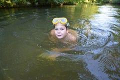 El adolescente del muchacho nada en el río en verano Imágenes de archivo libres de regalías