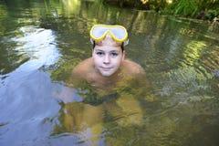 El adolescente del muchacho nada en el río en verano Imagenes de archivo