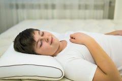 El adolescente del muchacho que duerme en la almohada y él anatómicos sonríe en su sueño Imagenes de archivo