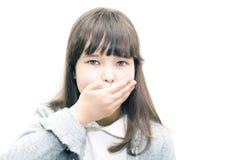 El adolescente del niño cubre su boca con su mano en un fondo blanco Fotos de archivo