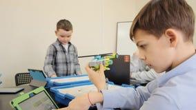 El adolescente demuestra el helicóptero plástico hecho por él en la cámara lenta de la lección que dirige almacen de metraje de vídeo