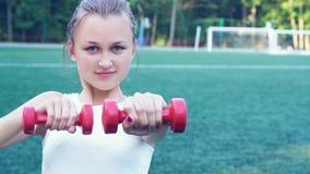 El adolescente deportivo hermoso entra para el iwith de los deportes una pesa de gimnasia del metal en el estadio Imagen de archivo libre de regalías