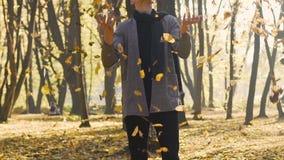 El adolescente despreocupado lanza las hojas amarillas en el aire, emociones positivas, felicidad almacen de video