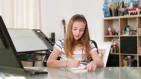 El adolescente dibuja algo en su cuaderno y negociaciones a sí misma metrajes