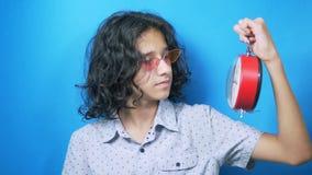 El adolescente divertido en vidrios rosados sostiene un reloj en sus manos, mira en ese entonces y se cierra la cara con su mano metrajes
