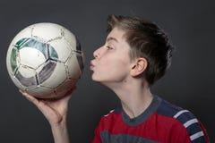 El adolescente divertido está besando un balón de fútbol Fotos de archivo libres de regalías