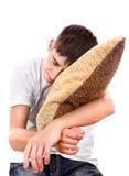El adolescente duerme con el amortiguador Foto de archivo