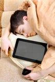 El adolescente duerme con la tableta Imagenes de archivo