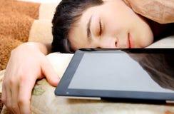El adolescente duerme con la tableta Foto de archivo